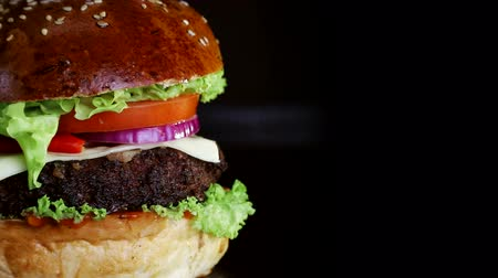 cuisine dark : Fast food. Burger with red pepper, slowly spinning on a wooden Board on a black background Stock Footage