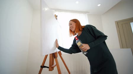 아크릴 : Woman artist begins to paint a picture. Wet the canvas with water, and prepares it for drawing.
