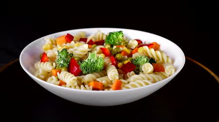 pimentas : Spiral pasta with vegetables on a plate revolve on a black background. Green cauliflower falls on a plate