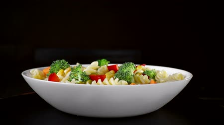пармезан : Spiral pasta with vegetables on a plate revolve on a black background