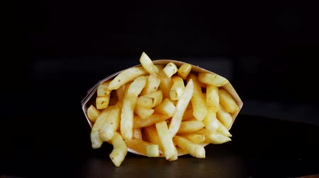 chips : French fries in a cardboard box on a black background revolves around itself. Fried potatoes