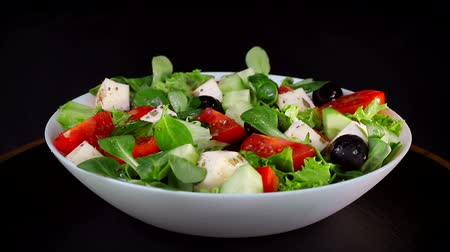 cherry domates : Healthy diet. Salad of greens and slices of cheese tomatoes and cucumbers. Plate rotates on a black background Stok Video