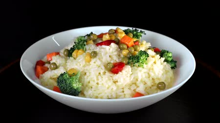 basmati : Rice with pieces of vegetables, greens and red pepper on a white plate rotates on a black background Stock Footage