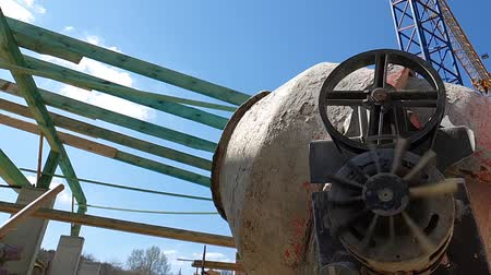 výřez : concrete mixer prevents concrete in slow motion, side view on the background of structures and blue sky Dostupné videozáznamy