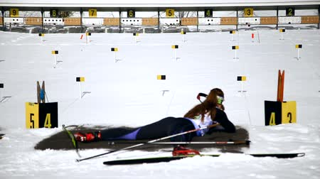pontão : Ukraine. Yavoriv. 12 march 2019. Biathlon competitions in the winter mountains. Athlete lying takes aim and fires at a target. Stock Footage