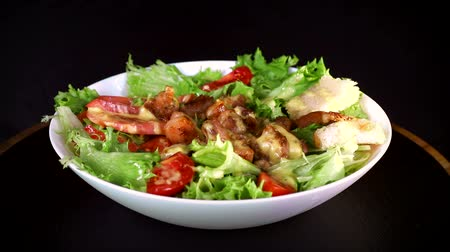 göğüs : salad with greens and pieces of meat, revolves around its axis in a white plate on a black background close-up
