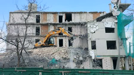 oszlopok : Ukraine. Lviv. 10 march 2019. Dismantling of the house with heavy machinery. A backhoe is destroying the house, dismantling it piece by piece