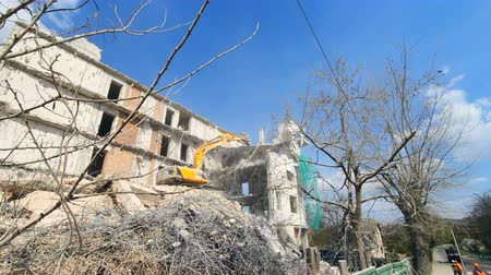demolishing : Ukraine. Lviv. 10 march 2019. Dismantling of the house with heavy machinery. A backhoe is destroying the house, dismantling it piece by piece