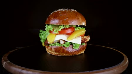 sezam : Burger with a large piece of meat, greens and cheese are spinning on a wooden Board on black background