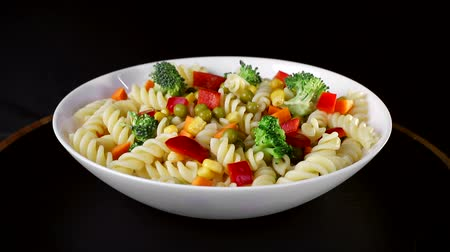 pimentas : Spiral pasta with vegetables on a plate revolve on a black background
