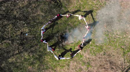 frizura : Aerail view on top. Group of children dancing around the fire holding hands