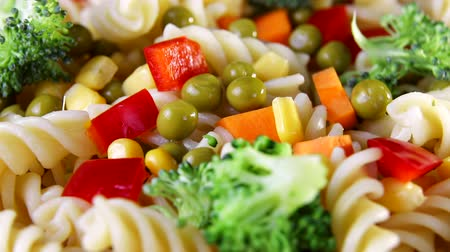 pimentas : Close up spiral pasta with vegetables on a plate revolve on a black background