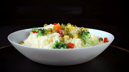 çeşnili : Rice with pieces of vegetables, greens and red pepper on a white plate rotates on a black background Stok Video