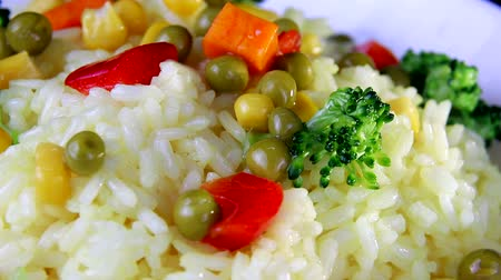 basmati : Rice with slices of vegetables close-up, greens and red pepper on a white plate spinning Stock Footage