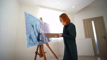 아크릴 : Woman artist begins to paint a picture with a spatula and acrylic paints. Creating a drawing on canvas