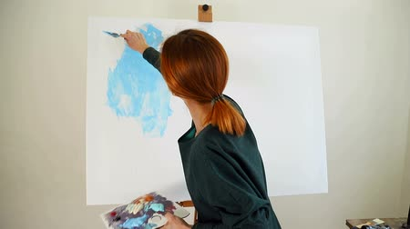 festett : Woman artist begins to paint a picture with blue acrylic paints with a spatula