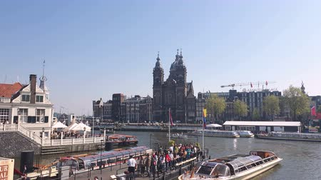 águas : Amsterdam, Netherlands. 25.04.2019. The Basilica of St. Nicholas in Amsterdam filmed from the waters of a canal. Amsterdam Netherlands. Push in shot.