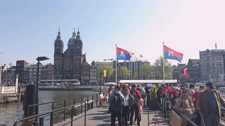 sinterklaas : Amsterdam, Netherlands. 25.04.2019. Queue of people who are waiting for a pleasure boat. The Basilica of St. Nicholas in Amsterdam filmed from the waters of a canal. Amsterdam Netherlands.