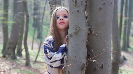 скрывать : little barefoot girl runs in a forest or Park and hides behind trees in a white dress with blue patterns.
