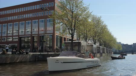 bezmotorové létání : Amsterdam, Netherlands. 25.04.2019. Old ships parked in the canals of Amsterdam. View from the tour boat. Shot with a wide angle lens