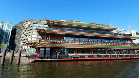 голландский : Amsterdam, Netherlands. 25.04.2019. Traditional chinese restaurant on the water in Sunny day. View from tourist boat