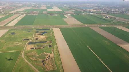 landing field : View from the window of the plane to Holland. Green fields and fields of tulips from the plane window