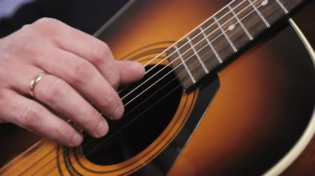 húr : A man plays an acoustic guitar. Close-up of the hand that hits the strings of the guitar
