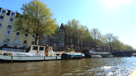 zaparkoval : Amsterdam, Netherlands. 25.04.2019. Old ships parked in the canals of Amsterdam. View from the tour boat. Shot with a wide angle lens