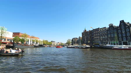скольжение : Amsterdam, Netherlands. 25.04.2019. Old ships parked in the canals of Amsterdam. View from the tour boat. Shot with a wide angle lens