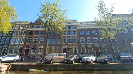 binnenstad : Amsterdam, Netherlands. 25.04.2019. Magnificent architecture of Amsterdam houses. The houses are tilted in different directions. The facades of the houses of Amsterdam on a Sunny day Stockvideo