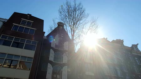 nizozemí : Magnificent architecture of Amsterdam houses. The houses are tilted in different directions. The facades of the houses of Amsterdam on a Sunny day. Glare of the sun shining into the camera