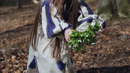 krans : A little girl in the woods picks up a whisk of white forest flowers, and puts it on his head Stockvideo