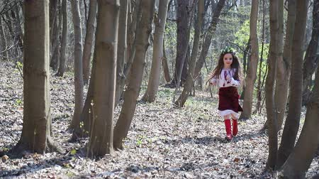 kamilla : girl in Ukrainian national costume, running through the spring forest between the trees in slow motion