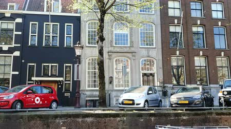 голландский : Amsterdam, Netherlands. 25.04.2019. Magnificent architecture of Amsterdam houses. The houses are tilted in different directions. The facades of the houses of Amsterdam on a Sunny day Стоковые видеозаписи