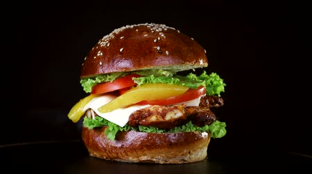 кунжут : Burger with a large piece of meat, greens and cheese are spinning on a wooden Board on black background