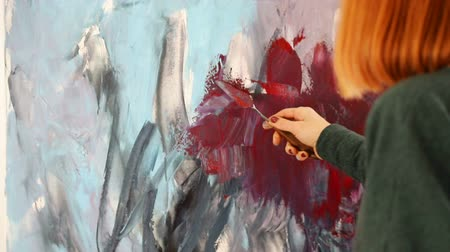 palette knife : The artist paints with Acrylic red and dark colors. Drawing with spatula and acrylic paints. Stock Footage