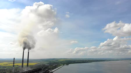 damp : Aerial view Pipe teleplastic that emit black smoke, on the background of beautiful nature, green fields and a large lake.