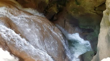 powódź : strong water flow in the cave. A small waterfall underground. The flow of water breaks between the stones