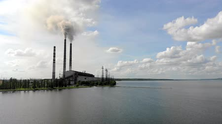 fabryka : Aerial view Dense thick smoke comes from industrial pipes Against the blue sky and nature and a large lake