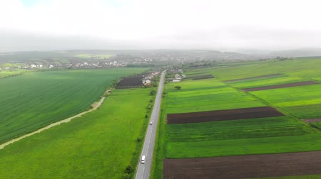 drive through : Aerial Flying over the road with cars separating the green fields. Foggy day and the Route that connects the city