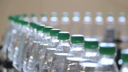megtöltött : white plastic bottles stand on the water bottling line, filled with mineral water, and clogged with green caps