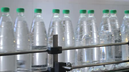 white plastic bottles stand on the water bottling line, filled with mineral water, and clogged with green caps