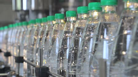 tampas : white plastic bottles stand on the water bottling line, filled with mineral water, and clogged with green caps