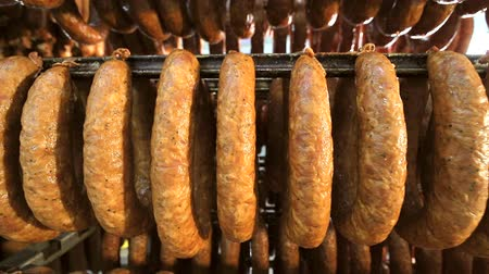 продукты : A batch of finished sausage in the form of rings, stored on the shelves in the production. A kind of sausage from the bottom to the top Стоковые видеозаписи