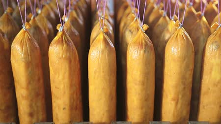 smoked : Mass production of sausage. Sausages are hanging on threads in a row.