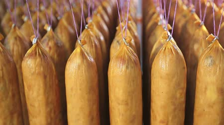 baharatlı alman sosisi : Mass production of sausage. Sausages are hanging on threads in a row.