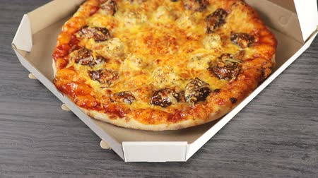 A mans hand opens a paper box in which there is a fragrant freshly baked pizza. Delivery of pizza in a box.