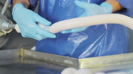 wołowina : Production worker in blue rubber gloves, makes sausage. A close-up of a sausage is created by an employee Wideo