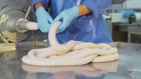 csip : Production worker in blue rubber gloves, makes sausage. A close-up of a sausage is created by an employee Stock mozgókép