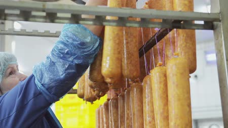 processed : An employee, a butcher, hangs fresh, freshly made sausage on the shelves for further firing in the oven.
